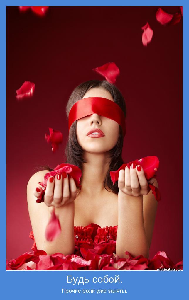 Фото Девушка, с завязанными глазами красной лентой, держит лепестки